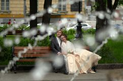 Bride and groom sitting in the park. With shot through the fountain splashes Royalty Free Stock Images