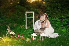 Bride and groom sitting in a park on the grass Royalty Free Stock Images