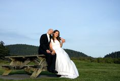 Bride & Groom Sitting On Picnic Table Royalty Free Stock Images