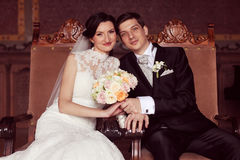 Bride and groom sitting on royal chairs Royalty Free Stock Images
