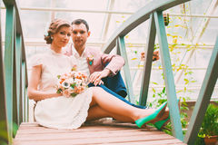 Bride and groom sitting on small bridge Royalty Free Stock Photos