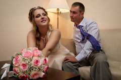 Bride and groom sitting on a sofa Royalty Free Stock Photography