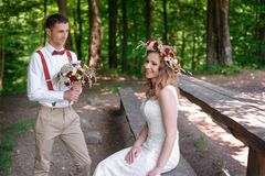 Bride and groom sitting in the summer park Stock Images