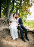 Bride and groom sitting under tree at river bank and kissing Stock Photography