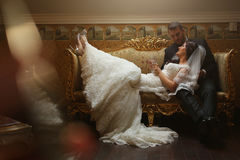 Bride and groom sitting on vintage sofa Stock Photography