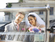 A bride and groom sitting in the wedding car Stock Photography