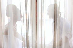 Bride and groom sitting in the window Stock Photo