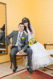 Bride and groom sitting on wooden chair Stock Photos