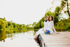 The bride and groom are sitting on a wooden pier near the pond Stock Photos