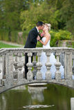Bride and groom on a small bridge in park Stock Images