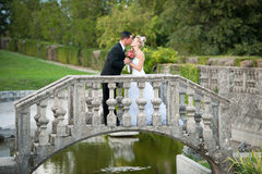 Bride and groom on a small bridge in park Royalty Free Stock Photos