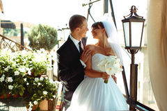 Bride and groom smile looking at each other while they stand in Royalty Free Stock Photography