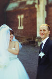Bride and groom smile standing apart behind an old cathedral Royalty Free Stock Image