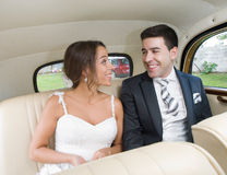 The bride and groom smiling inside a car. Stock Images