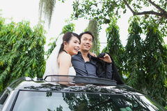 Bride and Groom Smiling Together While Standing in car Stock Photo