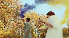 The bride and groom with smoke bombs on the background of trees stock footage