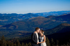 Bride and groom softly kissing. Amazing mountains view on background Royalty Free Stock Image