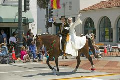 Bride and groom in Spanish outfits riding horse together during opening day parade down State Street, Santa Barbara, CA, Old Spani Royalty Free Stock Image