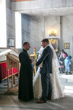 Bride and groom speak to priest. MOSCOW - MARCH 10: bride and groom speak to priest during orthodox wedding ceremony on March 10, 2013 in Moscow Stock Photo