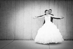 Bride and groom spreading arms bw Royalty Free Stock Image