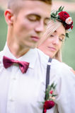Bride and groom stand behind each other with closed eyes Stock Images