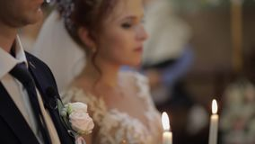 The bride and the groom stand in church, holding candles in their hands. The wedding ceremony of the bride and groom stock footage