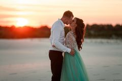 Bride and groom stand in desert at sunset, hug and kiss. Side vi Royalty Free Stock Photography