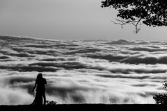 A bride and groom stand in front of a cloud inversion in Shenandoah Natioinal Park stock images