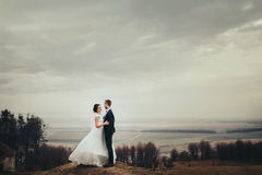 Bride and groom stand on the hill with great autumn landscape be stock images
