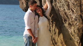 Bride and groom stand and hug in shallow water by cliff stock video footage