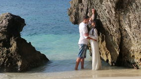 Bride and groom stand and kiss in shallow water by cliff stock footage