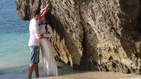 Bride and groom stand and kiss in shallow water by cliff. Bride in wedding dress and groom stand and kiss in shallow water by cliff stock footage