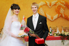 Bride and groom stand near banquet table Stock Photo