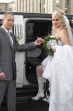 Bride and groom stand near a car Stock Images