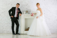Bride and groom stand  near fireplace Stock Image