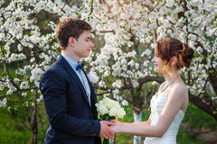 Bride and groom stand near a flowering tree in spring garden Stock Photo