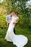 Bride and groom stand near a flowering tree in spring garden.  Royalty Free Stock Photo