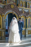 Bride and groom stand opposite the iconostasis. MOSCOW - MARCH 10: bride and groom stand opposite the iconostasis in the rays of light during orthodox wedding Royalty Free Stock Photography