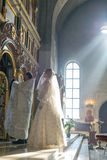 Bride and groom stand opposite the iconostasis. MOSCOW - MARCH 10: bride and groom stand opposite the iconostasis in the rays of light during orthodox wedding Royalty Free Stock Images