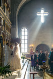 Bride and groom stand opposite the iconostasis in the rays of light. MOSCOW - MARCH 10: bride and groom stand opposite the iconostasis in the rays of light Stock Image