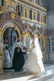 Bride and groom stand opposite the priest near iconostasis. MOSCOW - MARCH 10: bride and groom stand opposite the priest near iconostasis under the lightbeam Royalty Free Stock Photo