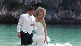 Bride and groom stand in shallow water at beach and put dress on water stock video footage