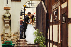 Bride and groom stand in a stone arch which leads to the street Stock Images