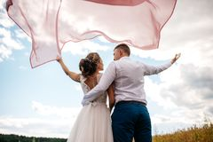 Bride and groom stand with their backs to the camera. royalty free stock images
