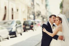Bride and groom stand thoughtfully somewhere on the street. A Royalty Free Stock Image