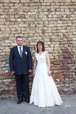 Bride and groom standing against brick wall Royalty Free Stock Photo
