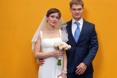 Bride and groom standing against wall Royalty Free Stock Image