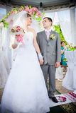 Bride and groom standing in alcove and holding hands Stock Photo