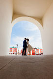 Bride and groom standing in the arch Stock Images