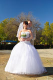 The bride and groom standing on autumn mall Stock Images